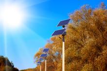 Row Of Solar Panels Near The Road Against A Blue Clear Sky.