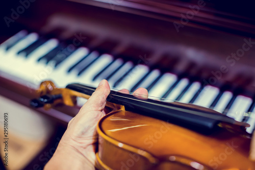 Hand playing the violin with blurry piano in music room or stage. music instrument concept. - 295180693