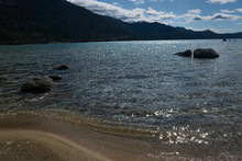 Late Afternoon Sunlight Stricks The Boulders And Sandy Beach In Lake Tahoe
