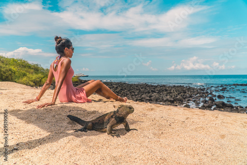 Fototapety, obrazy: Galapagos beach iguana and woman tourist on beach. Natural wildlife shot in San Cristobal, Galapagos. Beautiful beach with ocean sea background. Wild animal in nature.