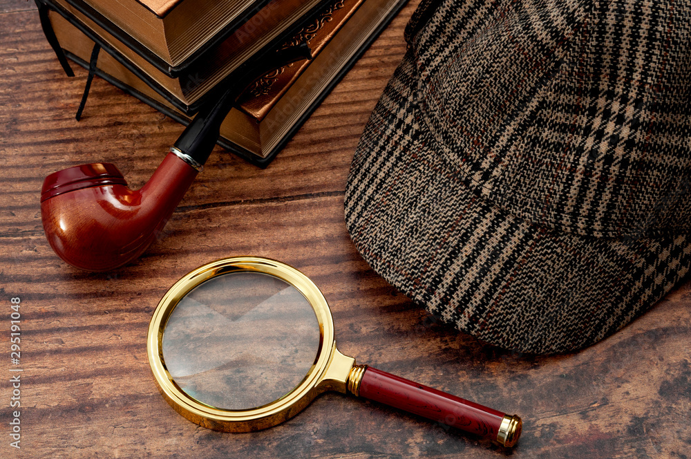 Fototapeta Literary fiction, police inspector, investigate crime and mystery story conceptual idea with sherlock holmes detective hat, smoking pipe, retro magnifying glass and book isolated on wood table top