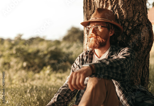 Fotografia  Thoughtful traveler resting near tree