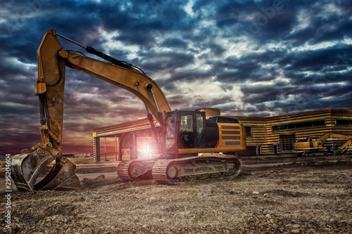Fotografía Excavating machinery at the construction site, sunset in background