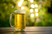 A Glass Of Cold Beer With A Foam On Top Placed On A Table In The Garden, The Background Is A Green Tree And Has Beautiful Bokeh At Dusk.