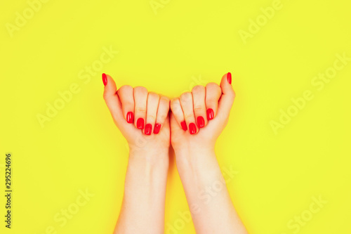 Poster Manicure Nails design. Stylish trendy female manicure. Beautiful young woman's hands on yellow background.