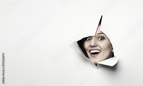Woman looking out from a hole of torn paper Wallpaper Mural