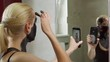 A woman in the bathroom near the mirror puts a black mud mask on her face and films herself on a smartphone camera, talking about the procedure.