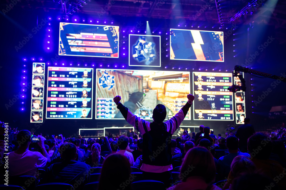 Fototapeta Big esports event. Video games fan on a tribune at tournament's arena with hands raised. Cheering for his favorite team.
