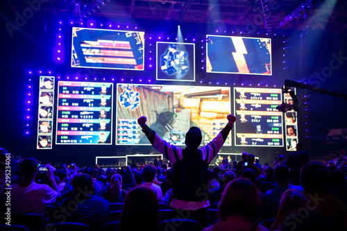 fototapeta na ścianę Big esports event. Video games fan on a tribune at tournament's arena with hands raised. Cheering for his favorite team.