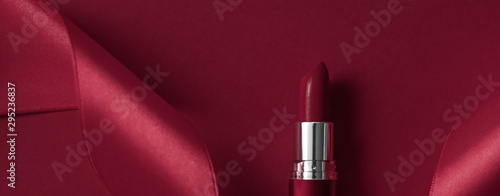 Fotografiet  Luxury lipstick and silk ribbon on maroon holiday background, make-up and cosmet