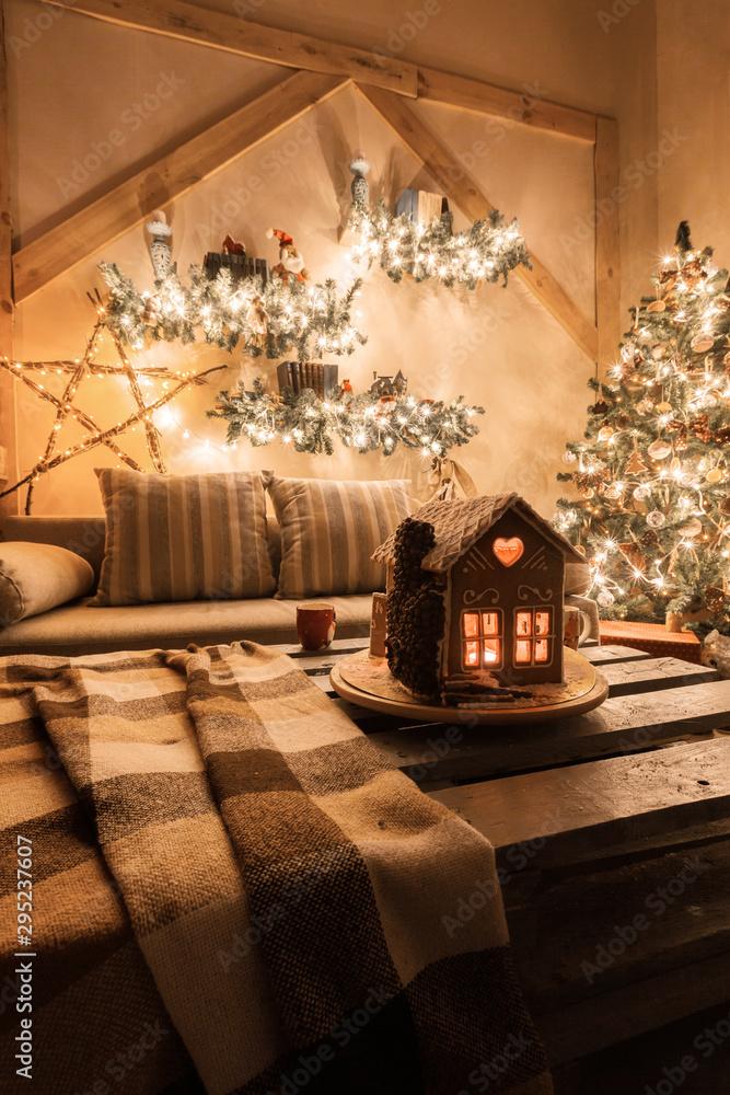 Obraz Christmas eve in the living room.. Homemade gingerbread house on background room decorated for Christmas. fototapeta, plakat