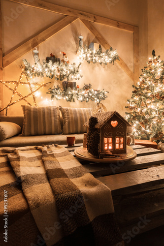 Obraz Christmas eve in the living room.. Homemade gingerbread house on background room decorated for Christmas. - fototapety do salonu