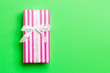 canvas print picture - Gift box with white bow for Christmas or New Year day on green background, top view with copy space