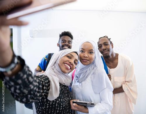 Fototapeta videographer in pink studio recording video on professional camera by shooting female muslim woman obraz na płótnie