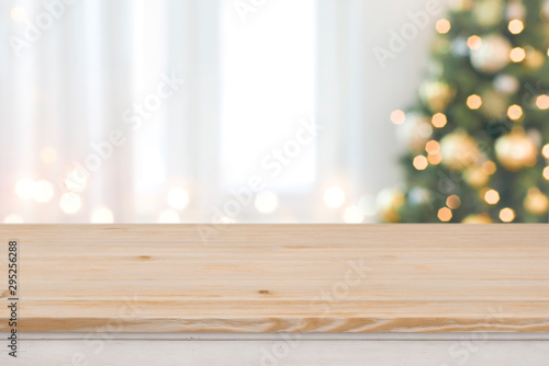 Fototapeta Christmas tree defocused background with wooden table in front obraz