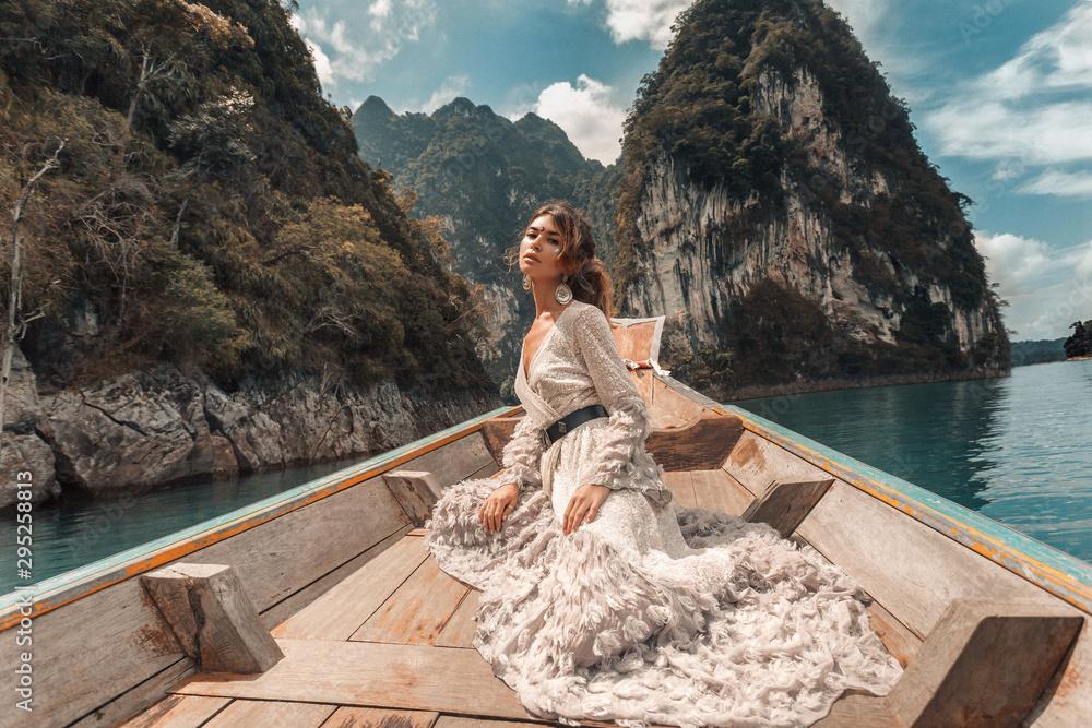 Fototapeta fashionable young model in elegant dress on boat at the lake