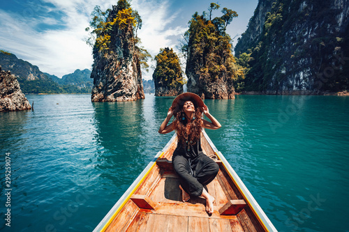 Photo happy young woman tourist in asian hat on the boat at lake