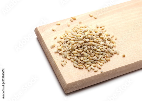 Valokuva  Peeled barley grains, kernels on wooden cutting, chopping board isolated on whit