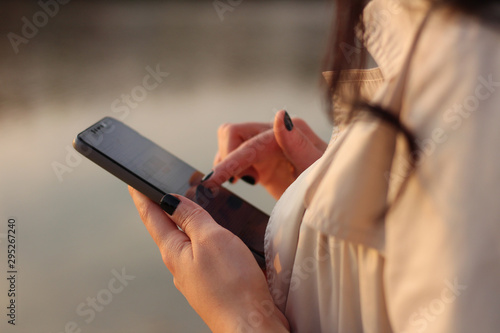 Fotografia, Obraz  White dark haired girl looks at the cellphone and swipes a finger on the phone s