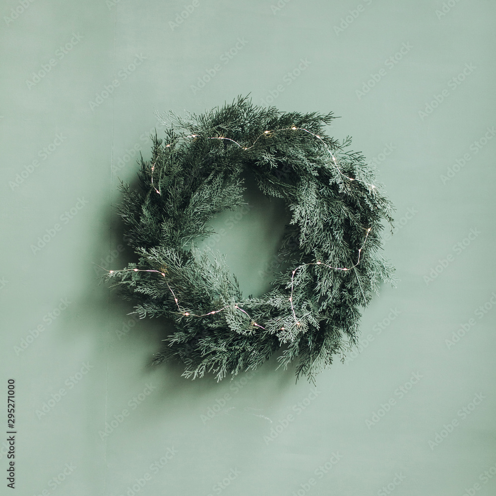 Fototapeta Christmas / New Year composition. Festive wreath made of christmas tree, fir branches against pale green wall. Minimal winter holidays concept.