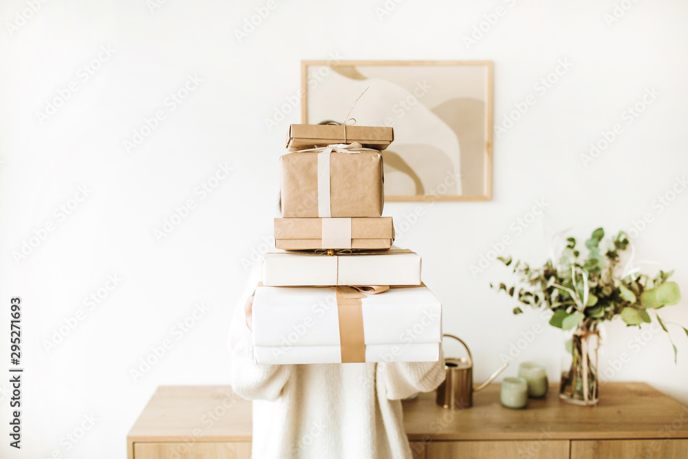 Fototapety, obrazy: Young pretty woman holding Christmas / New Year gift boxes with bows. Winter holidays gifts packaging concept. Flat lay, top view.