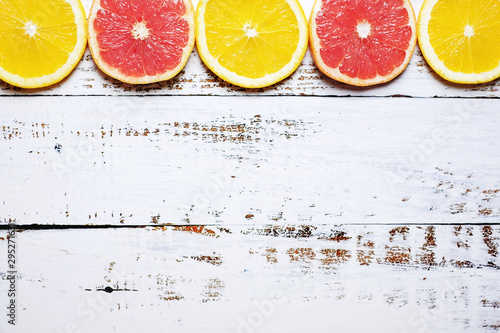 La pose en embrasure Jus, Sirop Orange and red grapefruit slices in a row on the white wooden background. Flat lay, top view, copy space