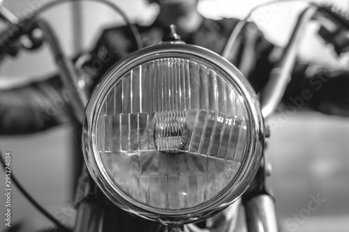 Fototapeta Details of an old retro motorcycle, classic vintage tech. chrome and restoration. collecting vehicles. black and white, bw. front lamp obraz na płótnie