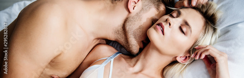 Fotografie, Tablou  panoramic shot of man kissing attractive woman with closed eyes