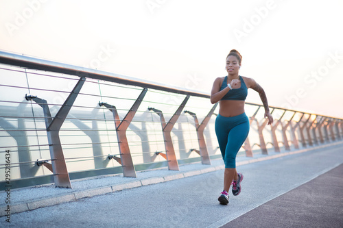 Fotografía Dark-skinned young overweight woman running really fast