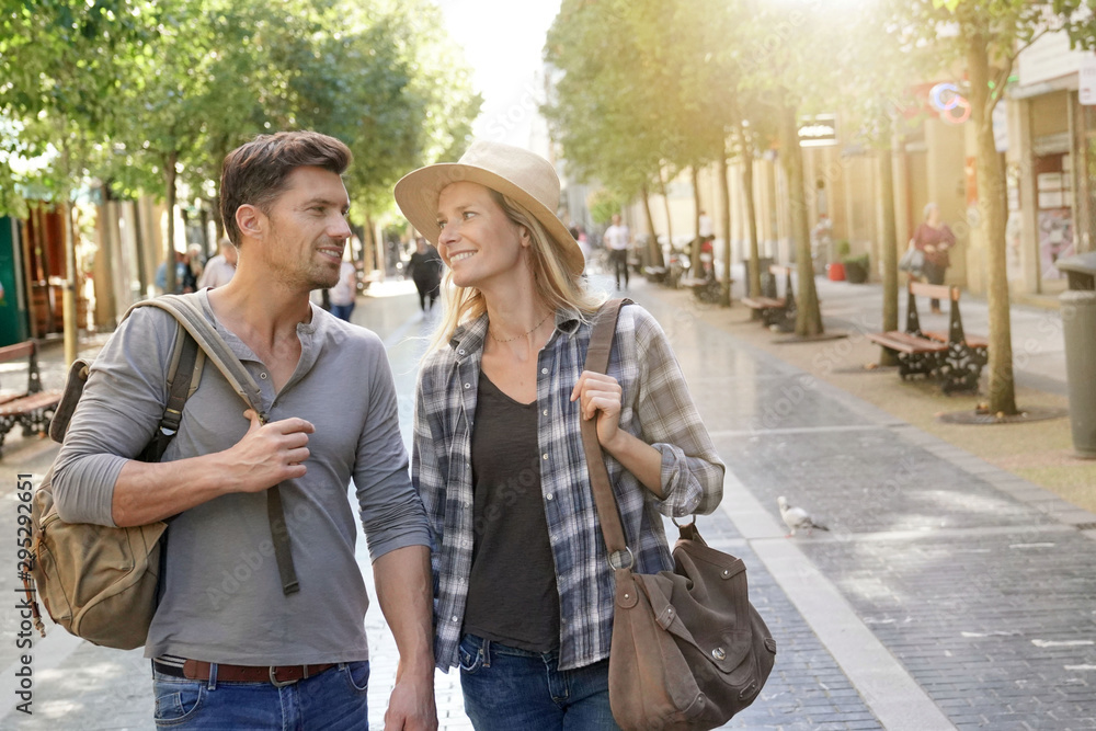 Fototapety, obrazy: Couple of tourists walking in shopping street