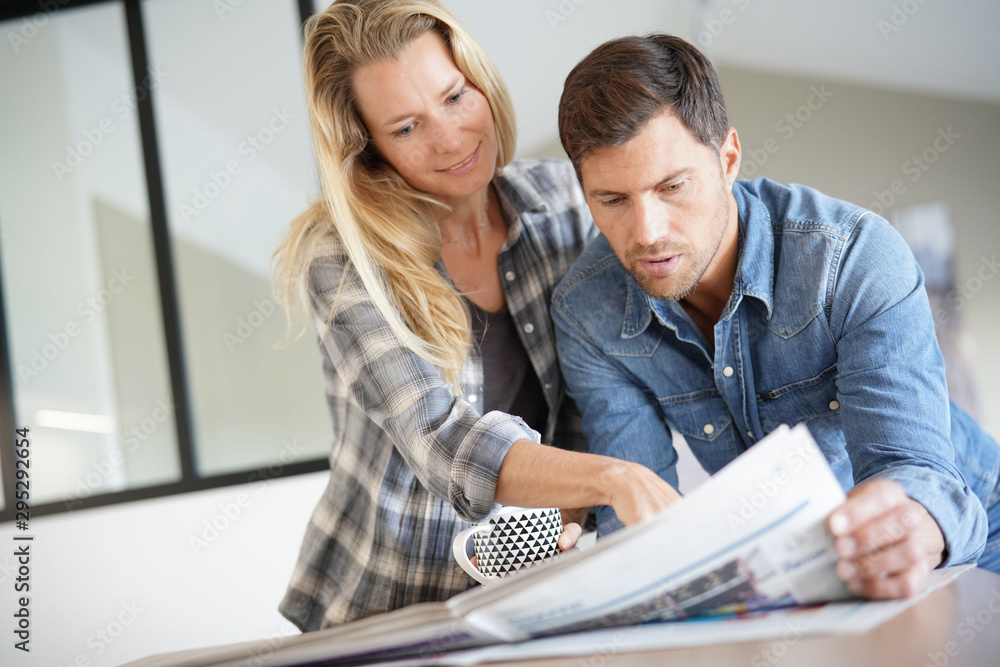 Fototapety, obrazy: Couple at home reading newspaper