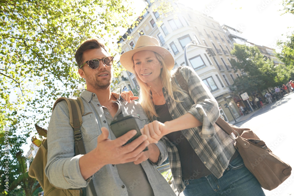 Fototapety, obrazy: Tourists connected with smartphone in European city