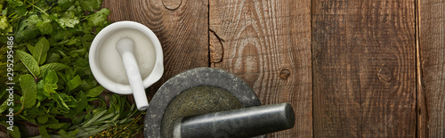 Fotografía panoramic shot of white and grey mortars with pestles on wooden surface with fre