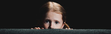 Panoramic Shot Of Frightened Child Hiding Behind Armchair And Looking At Camera Isolated On Black
