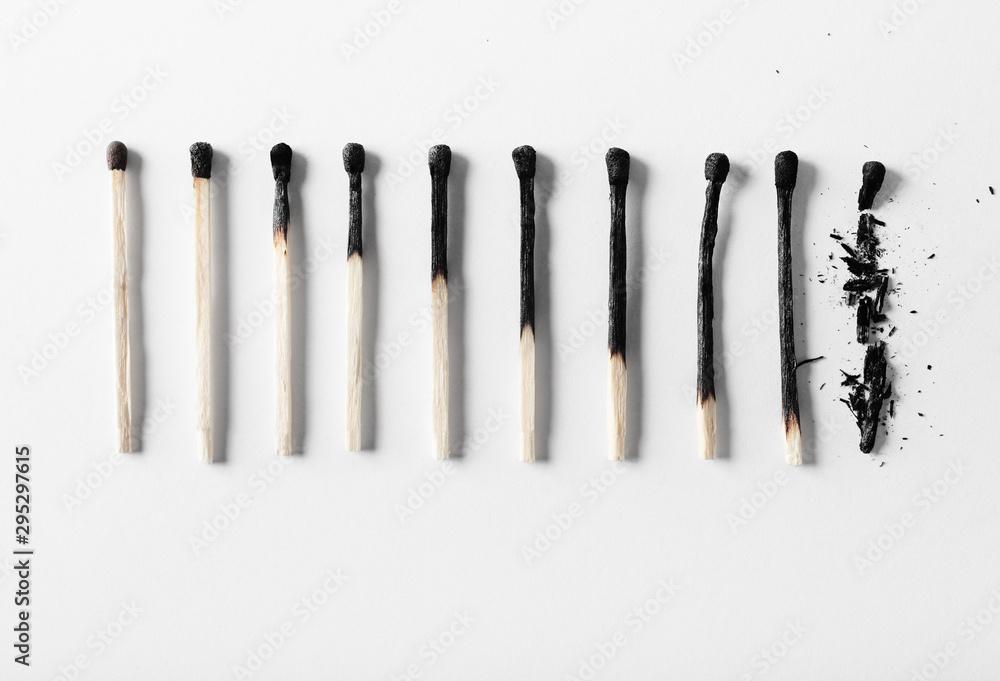 Fototapeta Aging process concept on the example of burnt matches on a white background.