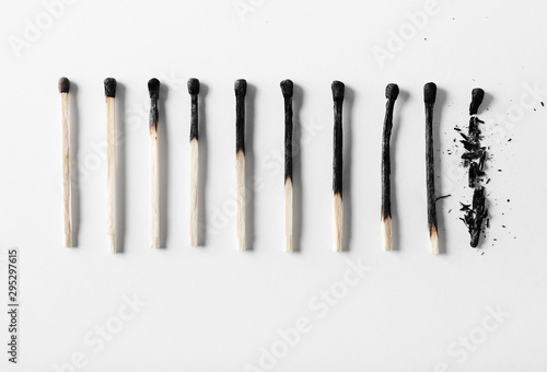 Leinwand Poster  Aging process concept on the example of burnt matches on a white background