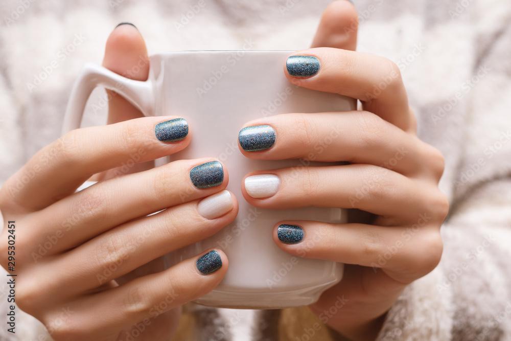 Fototapety, obrazy: Female hands with blue glitter nail design.