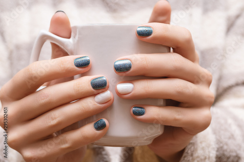 Pinturas sobre lienzo  Female hands with blue glitter nail design.