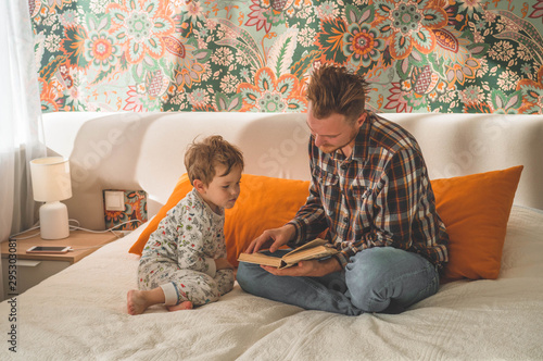Canvastavla  Dad and Son read a book together, smiling and hugging