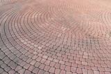Stone pavement in perspective. Stone pavement texture. Granite cobblestoned pavement background.