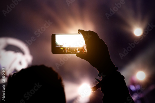 Smartphone in hands during music show. - 295304869