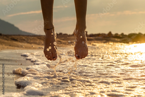 Photo Feet of a girl on the water of the beach