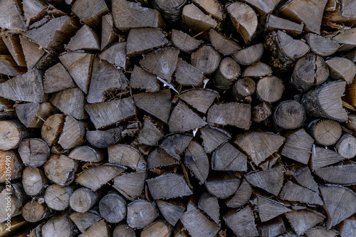 Close up of a stack of logs/wood from the end. Harvested firewood lies in the woodpil. background stack of wood