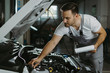 Young mechanic going through checklist in auto repair shop