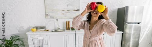 Fototapeta panoramic shot of happy woman holding red and yellow paprika