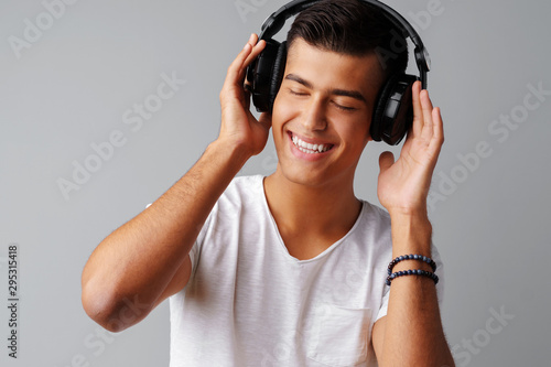 Young man teenager listening to music with his headphones over a grey background - 295315418