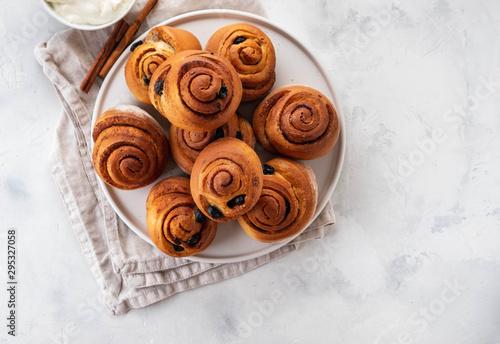Leinwand Poster Freshly Baked Traditional Sweet Cinnamon Rolls, Swirl on white plate