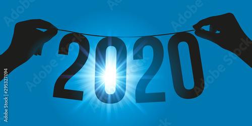 Carte de vœux 2020 présentant l'année 2020 suspendue face au soleil, sur une guirlande tenue par deux mains Canvas Print
