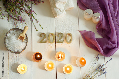 Metallic numbers 2020 on a background of white boards next to towels and sea salt for spa treatments, scented candles and a sprig of heather and lavender lie nearby