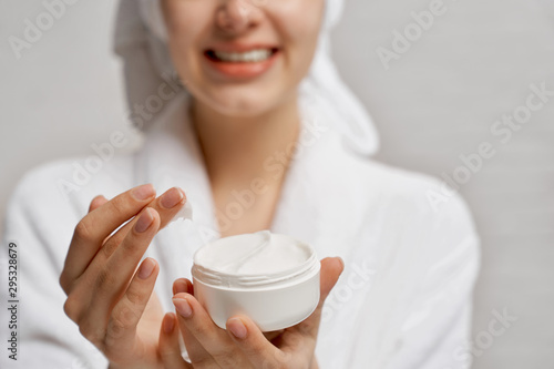 Young woman close up holding moisturizer and demonstrates. Fototapet